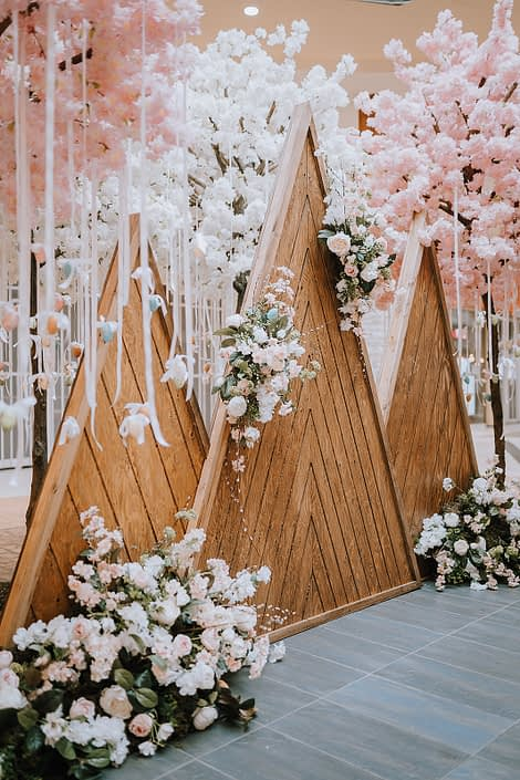 Wooden mountains decorated with white, peach and pink artificial flowers