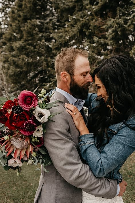 Rustic Boho Chic Wedding - Bride and groom standing together. Bride wearing a jean jacket holding bridal bouquet made of king protea, red peonies, pink roses, plum scabiosa, panda anenome, and eucalyptus greenery.