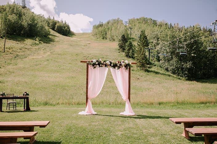 Tamara and Kyle's Rustic Chic Burgundy and Blush Wedding Outdoor Ceremony Archway - arrangement designed with Avignon Chyrsanthemums, White o'hara garden roses, white hydrangeas, quicksand roses, salal and eucalyptus.