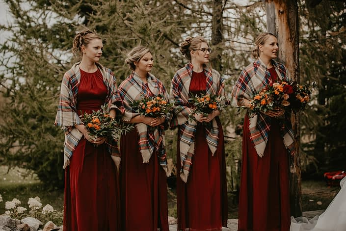 Hayley's rustic fall wedding bridesmaids wearing red dresses and plaid shawls and holding bouquets designed with orange spray roses, hypericum berries, italian ruscus and seeded eucalyptus.
