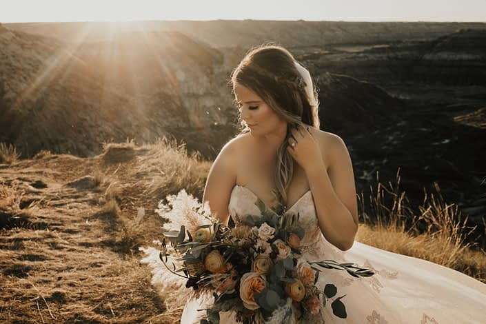 Boho Bride with peach and burgundy bridal bouquet at sunset in Drumheller desert