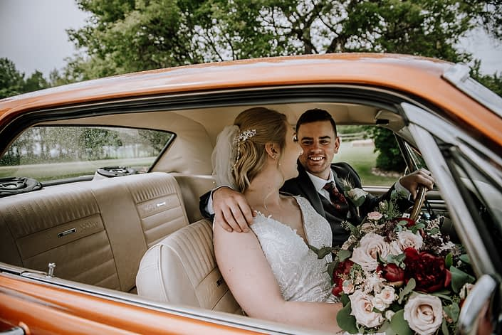 Bride and groom looking at each other sitting in an antique car; bride holding a rustic red and blush bridal bouquet designed with red charm peonies, quicksand roses, burgundy astrantia, light pink astilbe, and blush spray roses with eucalyptus greenery.