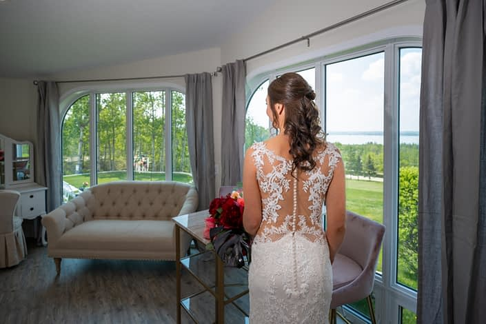 Hilltop wedding venue brida suite with bride in lace wedding dress with button down back and holding a bridal bouquet of burgundy peony and black monstera leaves