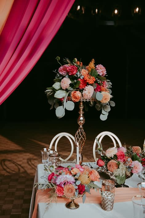 Tall arrangement featuring bold fuchsia and orange flowers such as dahlias, zinnias, and roses with eucalyptus greenery