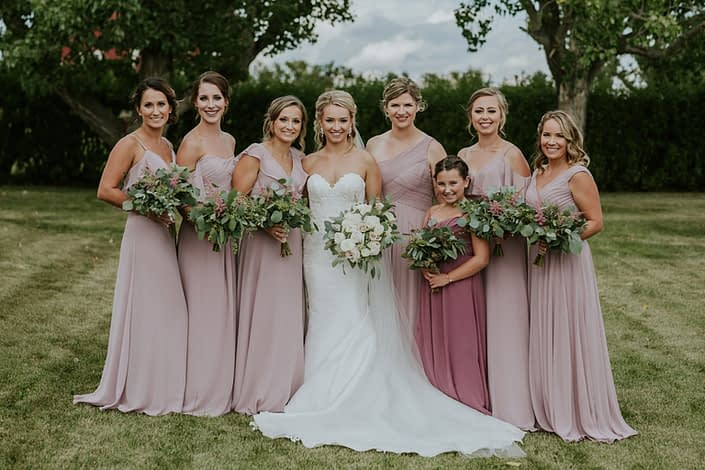 Rustic Chic Blush Wedding - Brooke wearing a white lace bridal gown and holding a blush and ivory bouquet made of roses, ranunculus and eucalyptus surrounded by her bridesmaids wearing blush floor length gowns and holding eucalyptus greenery bouquets with a touch of pink astilbe.