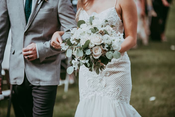 Bride walking down aisle with white and green bridal bouquet designed with astilbe, ranunculus, roses, sweet peas, gold painted scabiosa pods and eucalyptus
