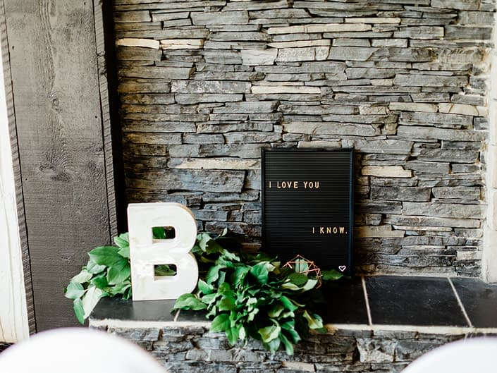 """Letter """"B"""", black letter board sign, geometric decor and lush greenery garland on a fireplace hearth."""
