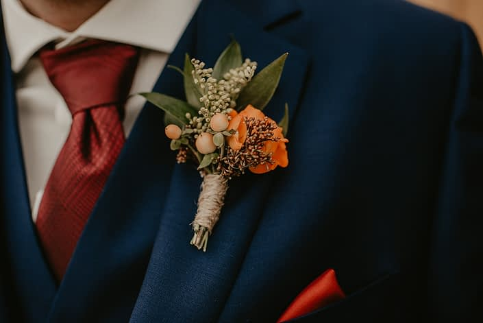 Rustic fall wedding boutonniere made of orange spray rose with hypericum, chocolate cosmos, solidago and seeded eucalyptus.