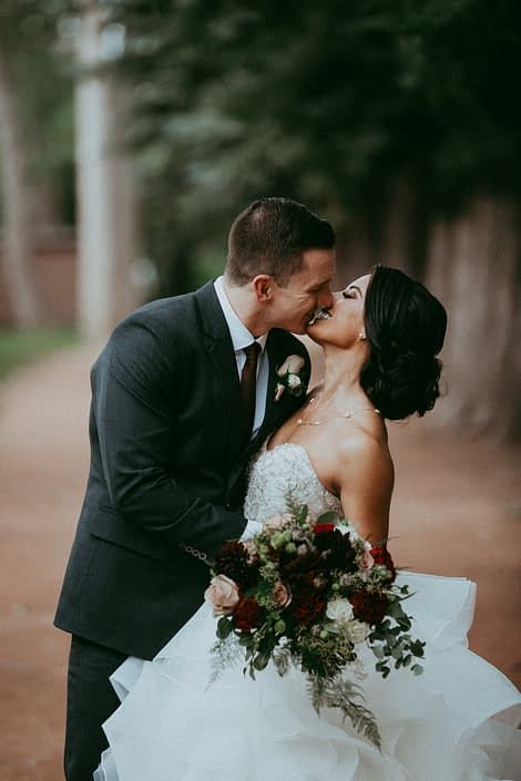 Bride and groom, Rikki Lee and Jake kissing with burgundy and mauve bridal bouquet featuring garden roses, dahlias and roses