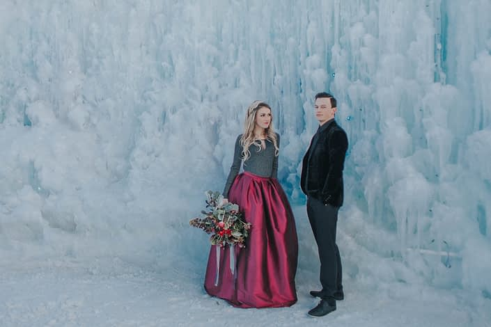 bride and groom engagement photoshoot at the ice castles with burgundy bouquet