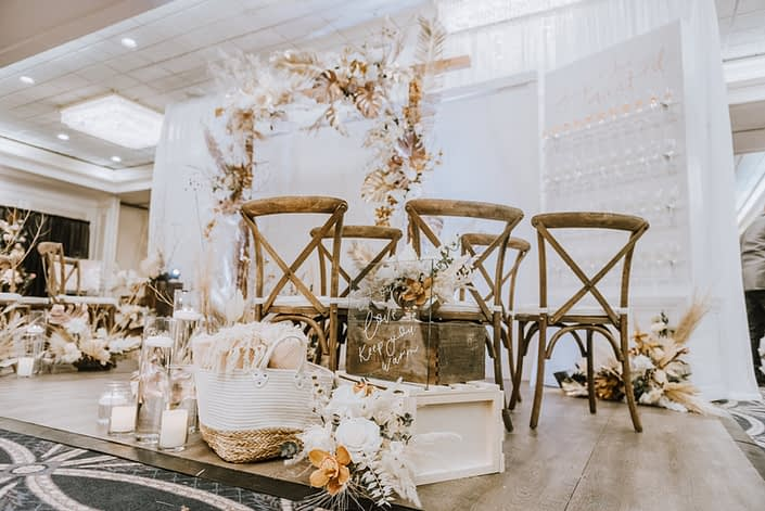 Let our love keep you warm sign, blankets, candles and flower arrangements made of dried leaves and branches, pampas grass, orchids and white roses.