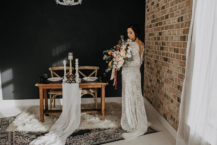 Neutrals Styled Shoot with Down the Aisle - Bride wearing lace gown holding a neutral coloured bouquet with ivory flowers and greenery tied with trailing ribbons.