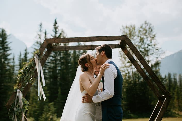 Bride and groom kissing at ceremony under a hexagon archway with greenery arrangement