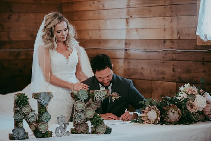 bride and groom at signing table at wedding with succulent monogram N and K and bouquets of King protea and eucalytpus