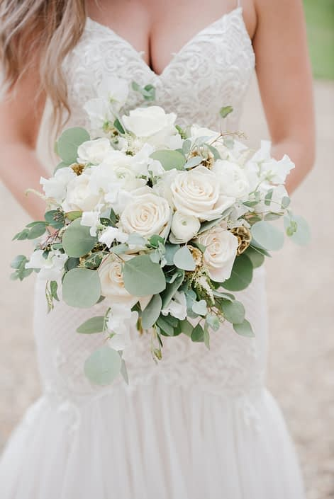 Natural white and green bridal bouquet designed with Tibet roses, white ranunculus, sweet peas, astilbe, gold scabiosa pods, gunni, silver dollar and seeded eucalyptus