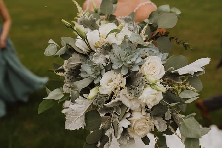 Vintage inspired bridal bouquet designed with white Playa Blanca roses, white lisianthus, white astilbe, Blue Star succulents, dusty miller, and a mixed variety of eucalyptus.