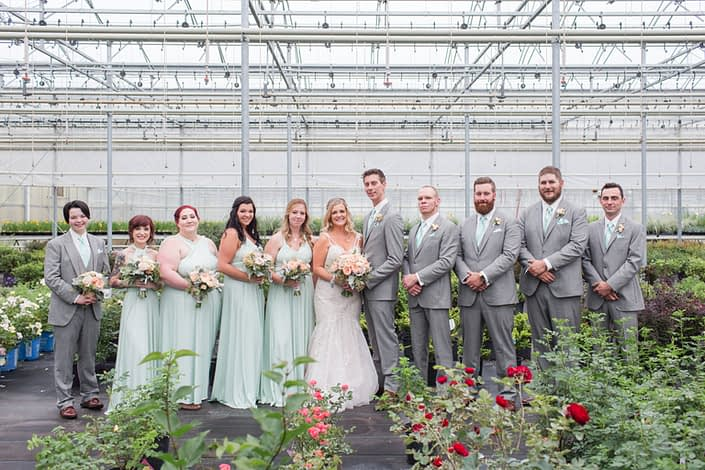 Megan and Steven's Rustic Pastel Wedding bridal party. The groom and his groomsmen are wearing grey suits with mint ties and blush pink boutonnieres. The bride is wearing a white embroidered bridal gown and is carrying a blush pink bridal bouquet. The bridesmaids are wearing mint floor length dresses and carrying blush pink bouquets.