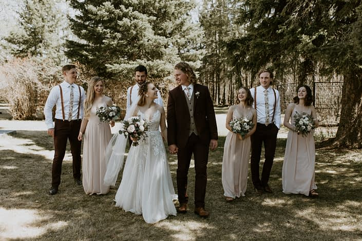 Emily and Jacob's Bridal party walking with blush, white and burgundy bouquets