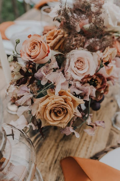 Modern boho florals in rust, terracotta and peach tones such as roses, lisianthus, and sweet peas