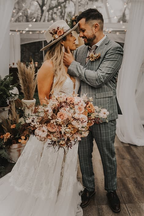 Modern Boho and Terracotta Couple with bridal bouquet, hat flowers and boutonniere; featured rust coloured flowers such as roses, cosmos, lisianthus and sweet peas