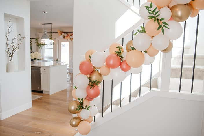 White and black stairwell with balloon garland accented by italian ruscus