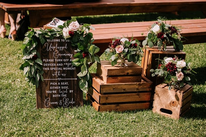 Rustic Chic Burgundy and Blush ceremony decor including fresh arrangements of roses and dahlias in a gold compote vase.