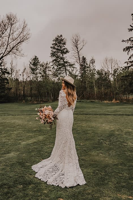 Modern boho bride wearing a lace gown and a boho hat with terracotta, rust and blush toned flowers