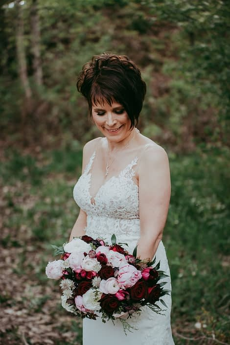Bride looking down at her elegant pink and burgundy bouquet made with Sarah Bernhardt peonies, burgundy Helleborus, blush and white ranunculus, black bacarra roses, blackberry scoop scabiosa, burgundy tulips, pale pink astrantia and eucalyptus.