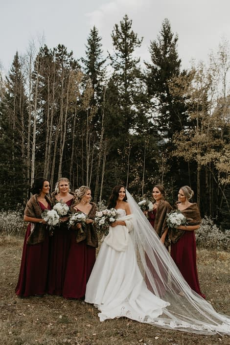 Brittany and her bridesmaids wearing fur shawls and holding ivory bouquets; bridesmaids wearing burgundy and brown shawls holding white hydrangea bouquets; bride wearing white gown and white fur shawl holding white and blush bouquet