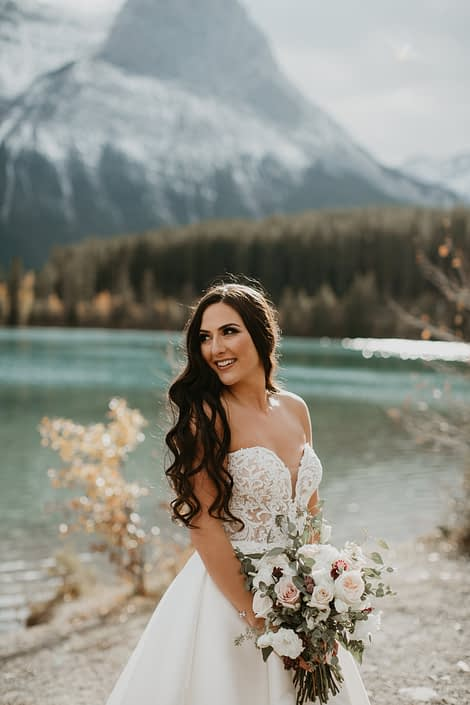 Brittany's elegant Canmore wedding bridal bouquet designed with white o'hara garden roses, quicksand roses, lisianthus, ranunculus, astrantia and gunni and seeded eucalyptus