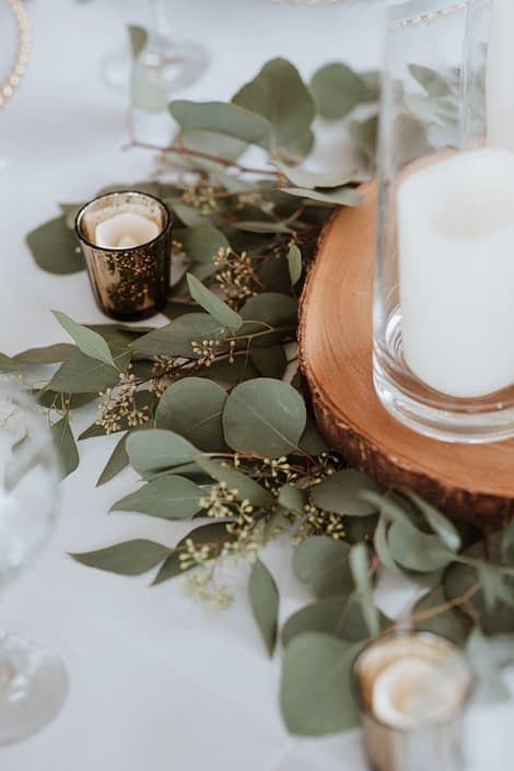 Fresh eucalyptus greenery centrepiece; silver dollar and seeded eucalyptus at the base of tree cookies with candles