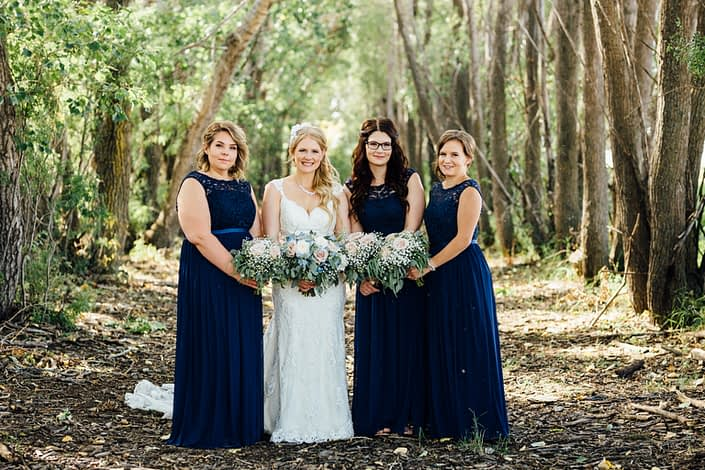 Bride and her bridesmaids holding bouquets featuring quicksand roses, white o'hara garden roses, succulents, delphiniums, babies breath and a mixed variety of eucalyptus greenery; bride wearing vintage inspired birdcage veil; bridesmaids wearing dark blue floor-length dresses.