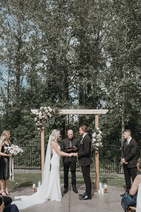 Archway arrangements on a wooden archway designed with astilbe, garden roses, peonies, poppies, ranunculus and roses in pastel tones such as white, yellow and pink
