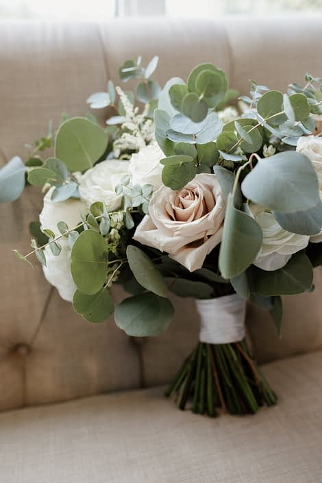 Rusty Rose Wedding Bridal Bouquet designed with white astilbe, white astrantia, white ranunculus, playa blanca roses, quicksand roses, white majolica spray roses and a mixed variety of eucalyptus greenery