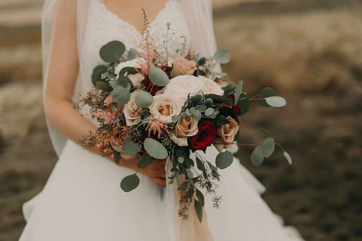 blush bridal bouquet with pops of red with red roses and quicksand roses and pink astilbe and blue eryngium and white o'hara garden roses and mixed eucalyptus in a loose and flowing style