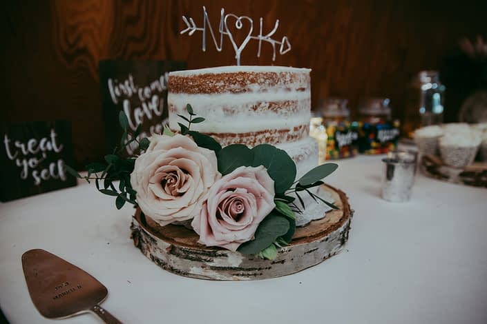 Rustic naked cake on birch wood cookie with N and K monogram and accent of eucalyptus and quicksand roses