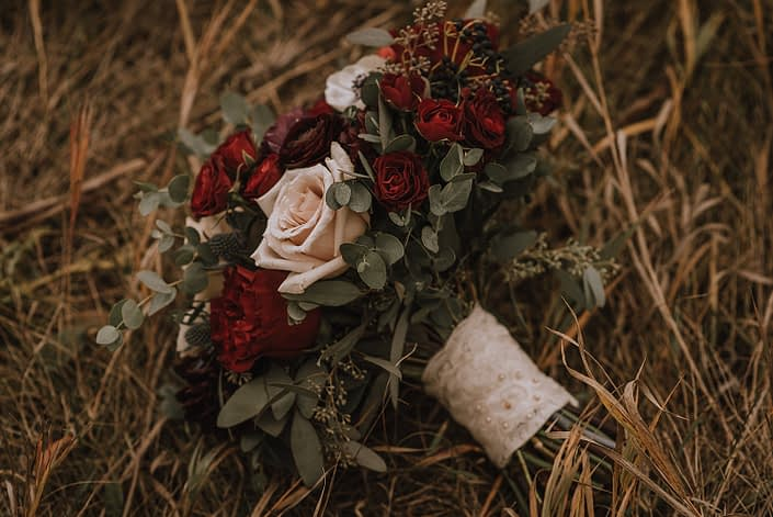 bridal bouquet designed with hearts garlden roses, burgundy ranunculus red spray roses eryngium and mixed euclayptus greenery, wrapped with ivory lace