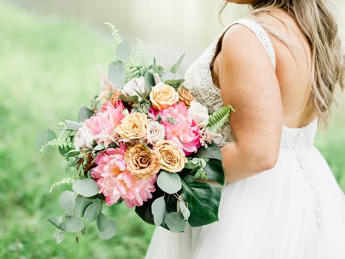 Modern Coral Charm Peony bouquet with monstera leaf, golden mustard roses, cappuccino roses, quicksand roses, boston fern and eucalyptus.