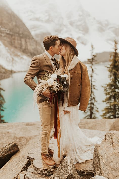 Moraine Lake Elopement Styled Shoot - couple kissing and girl wearing brown jacket and ivory bridal gown and hat holding pampas grass bouquet with blush roses and pops of red tied with trailing ribbons.