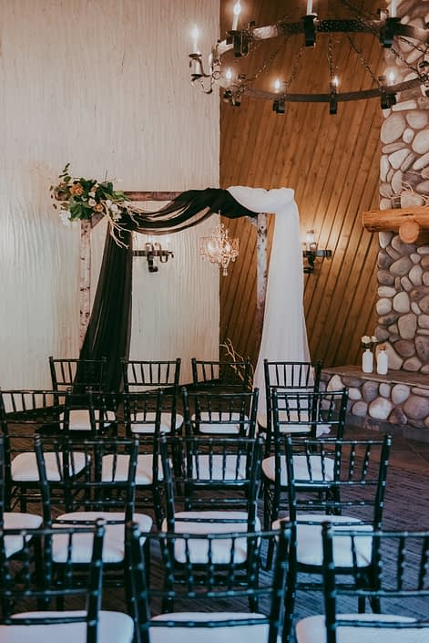 Black and white chiffon draped on a birch archway adorned with a corner floral arrangement of mazanita branches, tulips, quicksand roses and toffee roses.