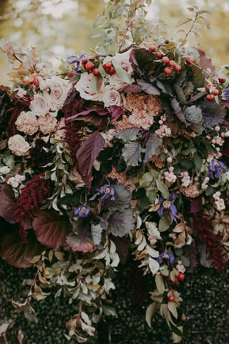 Boxwood wall with foraged greenery and kale, burgundy amaranthus and blush carnations and roses