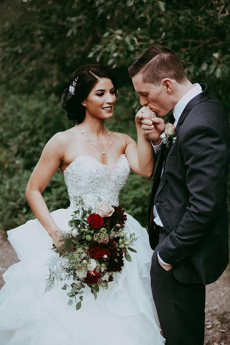 Groom kissing bride's hand with burgundy and mauve bridal bouquet designed with garden roses, dahlias and roses