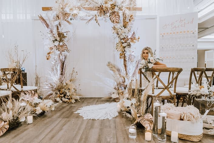 Down the Aisle Wedding Show 2020 model sitting and holding pale pink and white bouquet surrounded by arrangements made of dried leaves and branches, pampas grass, metallic gold painted monstera leaves, Japanese white sweet peas, quicksand roses, and painted sago palm.