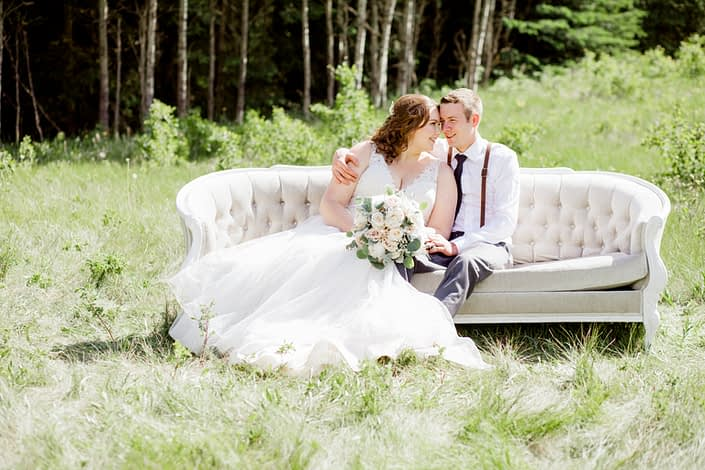 Kuera and Mark in a field on a vintage linen tufted sofa; bride is holding a cream and blush bouquet designed with white o'hara garden roses, white peonies and grey toned greenery.