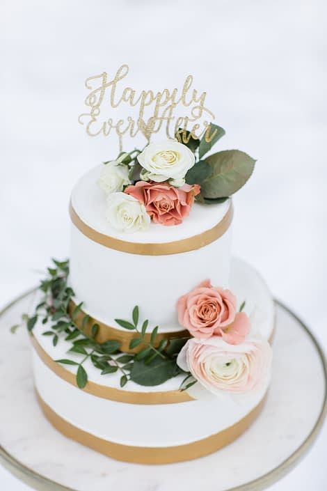 winter wedding cake with white fondant and gold trim accented by gunni eucalyptus, peach spray roses and ivory hanoi ranunculus