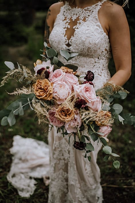 bride in white lace wedding dress holding organic oblong bridal bouquet designed with gold plumosa, cinerea eucalyptus, toffee roses, plum ranunculus, pale pink peony and pink ohara garden roses