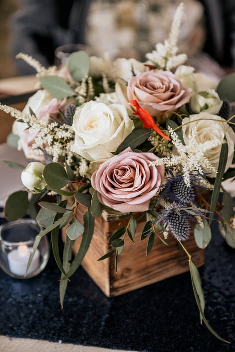 Mauve, ivory and navy flowers such as amnesia roses, playa blanca roses, white o'hara garden roses, astilbe and eryngium in a wooden box