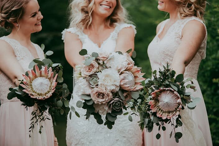 bride and bridesmaids in blush lace holding bouquets of king protea, eucalyptus and white peony and blush roses