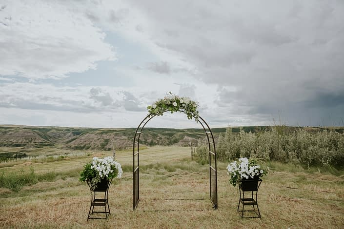 Archway in a field decorated with a flower arrangement at the centre made with white hydrangeas, white o'hara garden roses, playa blanca roses, quicksand roses, eucalyptus, Italian ruscus and salal.