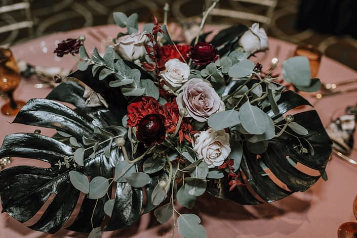 Cambridge Bridal Show 2020 - low centrepiece with black monstera leaves, red roses, blush roses, red ranunculus and eucalyptus greenery.